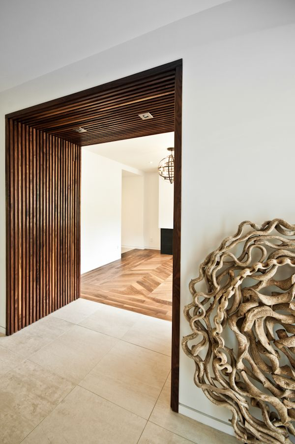 ScanWest Doors - STRAIT: A custom-made alcove integrating two invisible doors (powder and closet doors) with surrounding wall panels. The wood is oiled solid Black American Walnut
