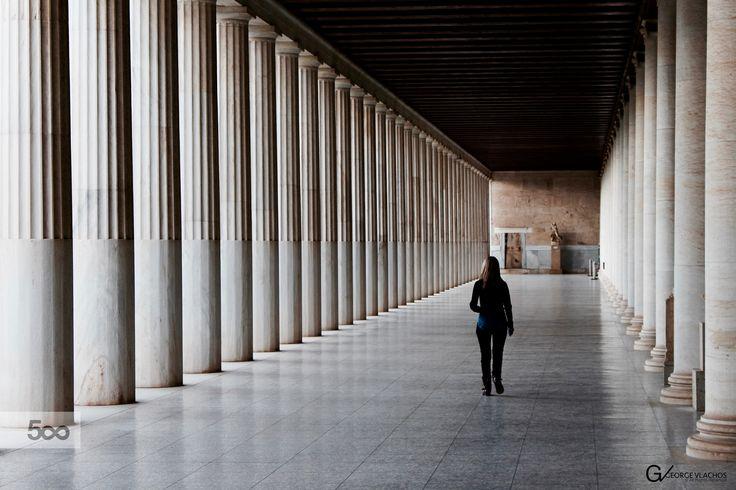 Walking through the columns at the Stoa of Attalos in Athens, Greece.