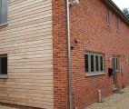Bovingdon bricks zinc downpipe and paler grey timber frame windows