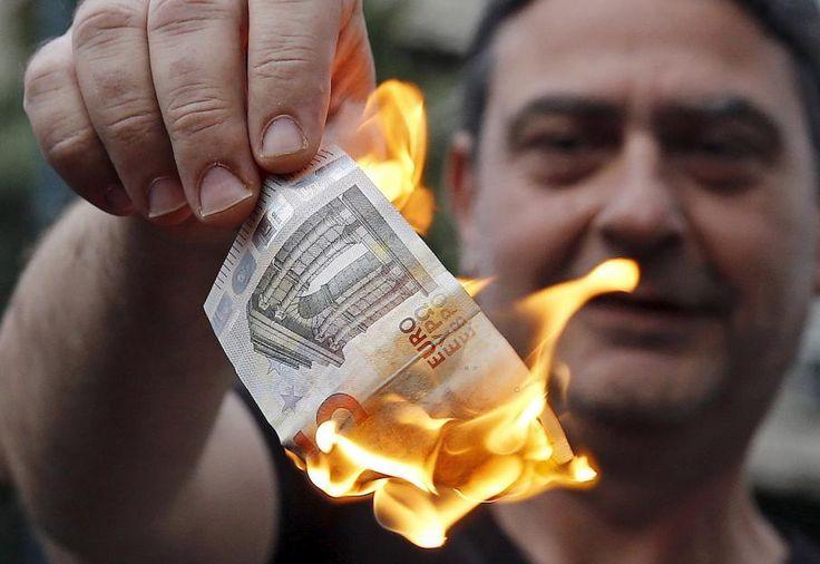 La monnaie européenne, symbole de la colère des Grecs. Un manifestant anti-austérité brûle un billet de 5 euros, le 28 juin 2015 à Athènes (Grèce).  ALKIS KONSTANTINIDIS / REUTERS