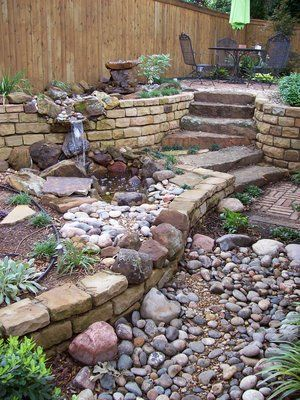 "Nice brick wall, with openings made by ""falling"" rock. Nice stairs and ""dry river bed"" too.Lots of inspiration here."