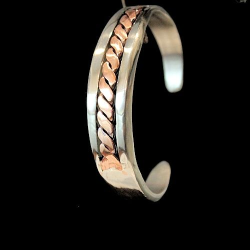 Men's or women's solid stainless steel bracelet.  This piece measures 5/8″ wide, and has a section removed and then replaced with twisted 13ga copper wire that has been flattened. This bracelet is sure to make a statement as it will shine in any light that it comes into contact with. As in all of our stainless steel jewelry, we use a very high grade of stainless steel and then we polish to a mirror finish, so in most cases our  stainless steel jewelry will outshine silver jewelry.