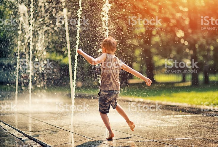 Summer in the city - little boy playing with fountain royalty-free stock photo