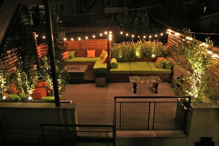 This secluded space is protected by fences and offers plenty of space for seating and entertaining. Small trees and shrubs complement the choice of bright green upholstery and strings of lights add a touch of whimsy.