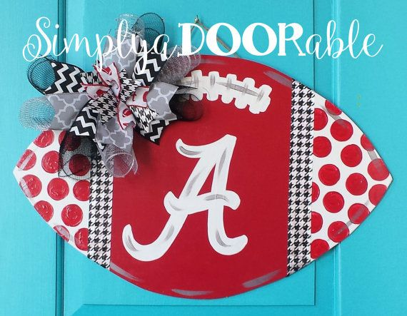 ROLL TIDE!!! This Alabama Football is Simply aDOORable. Perfect for football season, tailgate parties & Alabama fans everywhere! Wood football door hanger in crimson, white, houndstooth and silver with the Alabama Logo on the front. The football is painted black on the back for a finished looked and comes with an adjustable jute hanger.  I love to do footballs and am happy to do any school, please message me for information. Football is 24 wide x 15 tall and is made of 1/4 Baltic Birch…