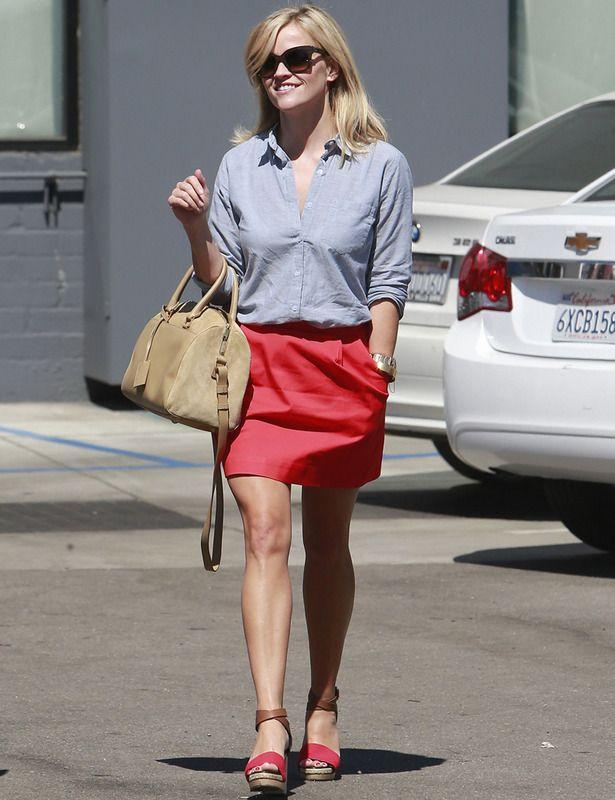 La actriz Reese Witherspoon está perfecta con esta falda tulipán en rojo que combina con una camisa básica en azul, sandalias bicolor y bolso de mano en nude.