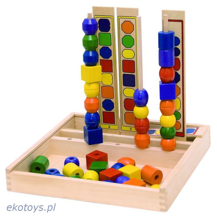 Układanka logiczna.  Zadaniem dziecka jest nawleczenie na drewnianą listewkę korali, w taki sposób aby zgadzały się one z narysowanym wzorem. Dziecko musi więc wziąć pod uwagę zarówno kolor kształt jak i kolejność korali aby prawidłowo wykonać zadanie.