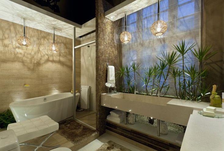 O banho do casal é o ambiente criado por Maristela Broilo, que substituiu limestone e madeira por porcelanato, usou pastilhas de vidro reciclado e madeira de demolição; a iluminação emprega LEDs. Mostra Morar Mais por Menos Belo Horizonte