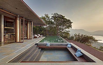 Obývací pokoj a jídelna s kuchyní v jednom jsou porpojeny s venkovní terasou, kde je kromě bazénu zanořené posezení.