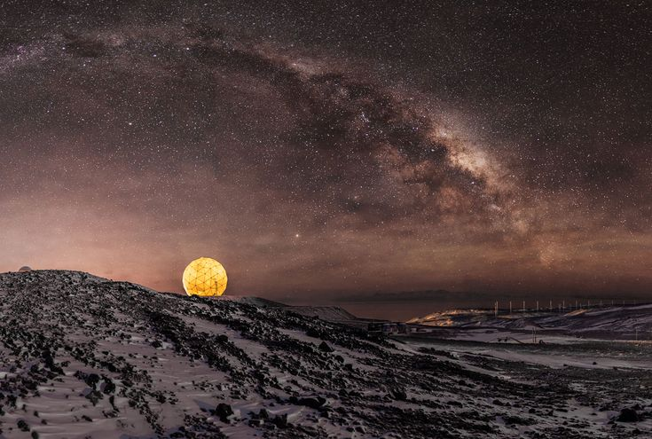 "The Milky Way shines above in the night sky near McMurdo Station on June 6, 2016. Below is the site of the NASA Near Earth Network satellite dish, known locally as the ""golf ball,"" which is one of three U.S. space communications networks collecting data from polar-orbiting satellites."