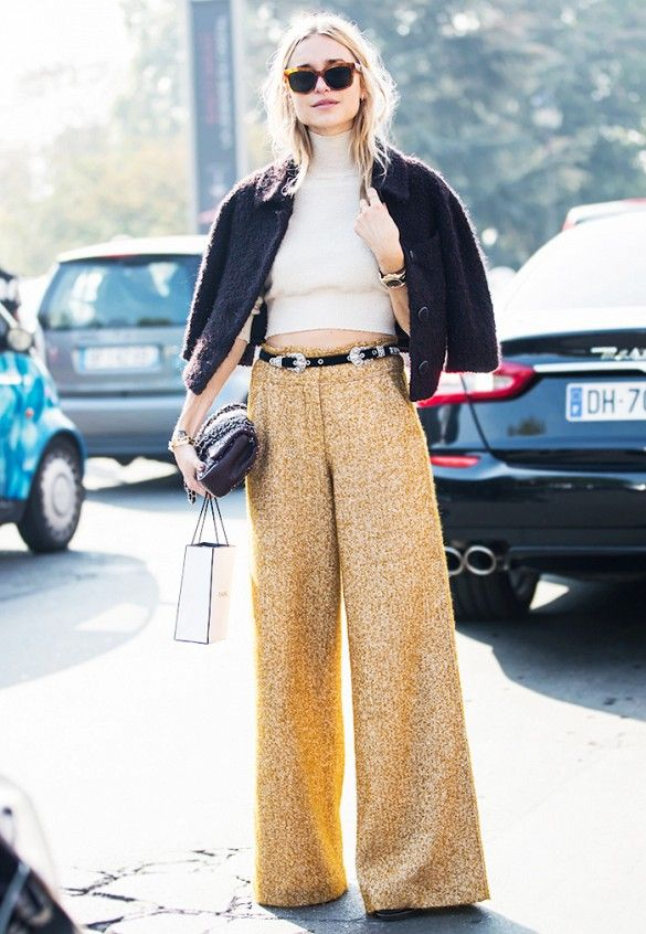Pernille Teisbaek wears a cropped turtleneck, belted wide-leg trousers, a cropped black jacket, clutch, and tortoiseshell sunglasses