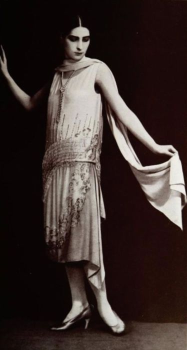 Воздушное платье с золотыми вставками, цветами и белым жемчужным ожерельем.