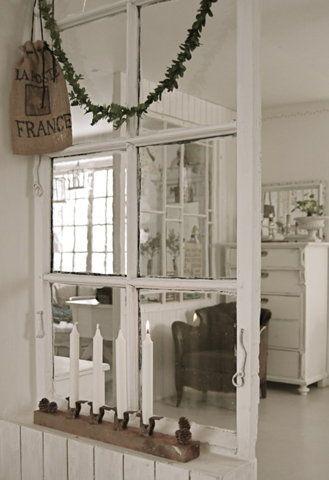 Indoor windows create interest and contrast between two rooms