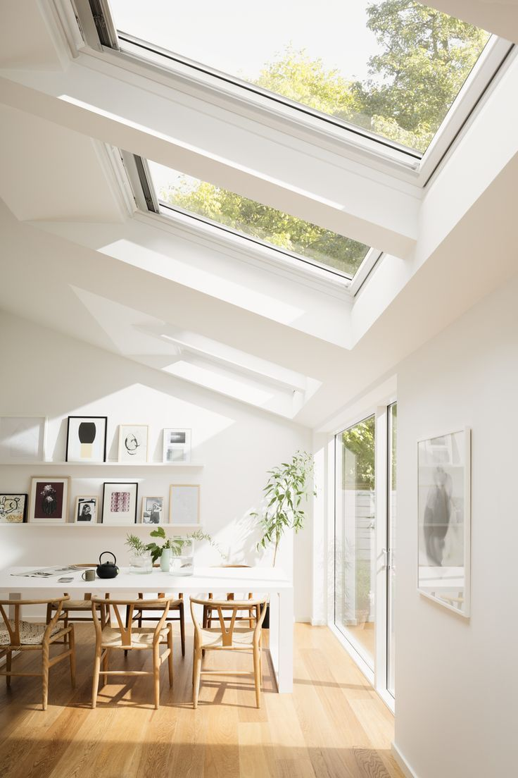 Bright Scandinavian dining room with roof windows and increased natural light…: