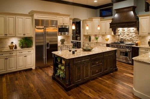 Great combination - cabinet style is very cool classic with a nice dark/light contrast, awesome range hood with stone backsplash, stainless appliances, nice counter tops, tile backsplash, and nice hardwood floors. Lighting over the island is the only disappointment.