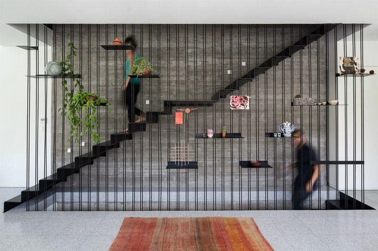 Industriální šeď doplňuje černé kované schodiště, které díky své subtilní konstrukci a efektnímu zábradlí kraluje celému domu.