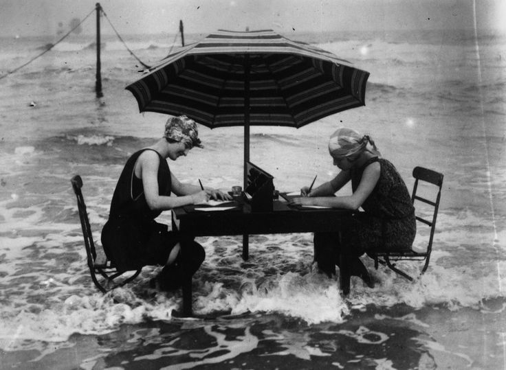 alta marea - 1925 - General Photographic Agency. Two women brave the lapping waves at their feet as they continue with their correspondence  at the water