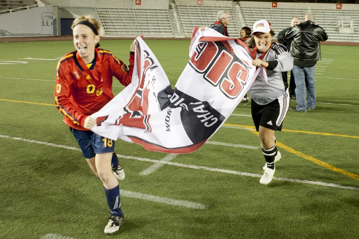 Jacqueline Tessier and keeper Chantel Marson carry the national championship banner after defeating Montreal for the second title in as many years