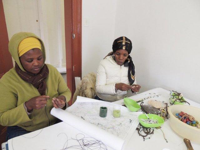 Stringing handmade beads into lanyards