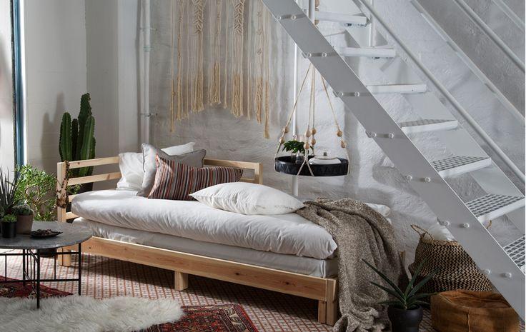 Diván de pino macizo sin tratar con ropa de cama de color blanco y beige. Se puede abrir para utilizarlo como cama de matrimonio por la noche.