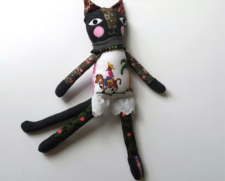 This cat doll is named Kali (meaning energetic one). She is a one of a kind, handmade art doll.She measures approximately 46 cm (18 inches) tall from tip of her ears to toes.Kali has a beaded necklace and buttons that secure her arms to her body and is therefore most suitable as a decorative piece. However with gentle play she could be enjoyed as a toy for a child over the age of 5 years old. NB The doll stand is not for sale.CONSTRUCTIONBody: up cycled vintage emb...