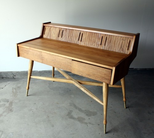 """Mid century walnut writing desk by Mainline for Hooker. Very sturdy with four oak turned legs with brass caps and cross brace. Plenty of storage up top behind four sliding wood panels, and three middle supply drawers. SOLD    48"""" wide. 36.5"""" tall. 24""""deep.    Delivery available for your home or business."""
