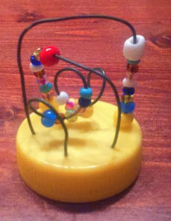 I found  the original idea at Pinterest - and I had to realize it. But I used for the base a plastic cap instead of polymer clay. I love it,  even it is a Baby toy but in miniature.  ciaoverde.blogspot.hu .
