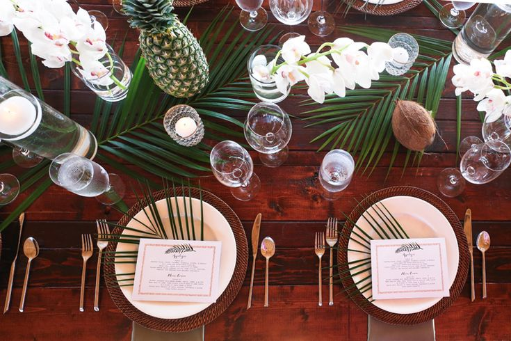 Tropical beach wedding reception tablescape with pineapples, palm fronds and orchids (Lifelong Photography Studio)