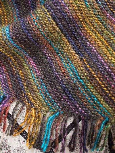 """Knit from one narrow point to the full width and back down again, this simple garter stitch shawl uses dropped stitches to easily add fringe. Knit with 2 skeins of #4 worsted-weight Berroco® Millefiori™ """"Viola"""" using a U.S. size 7/4.5mm 29"""" circular needle. Finished size is 44"""" x 17"""", excluding fringe."""