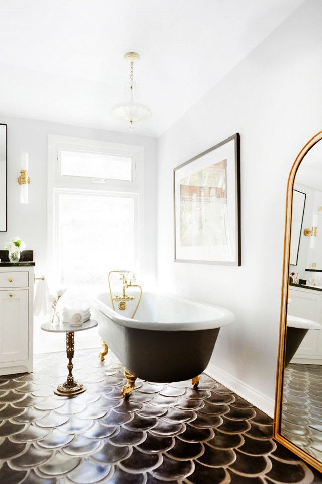 A bright bathroom with gray fish tile floors, a gold mirror, and a clawfoot