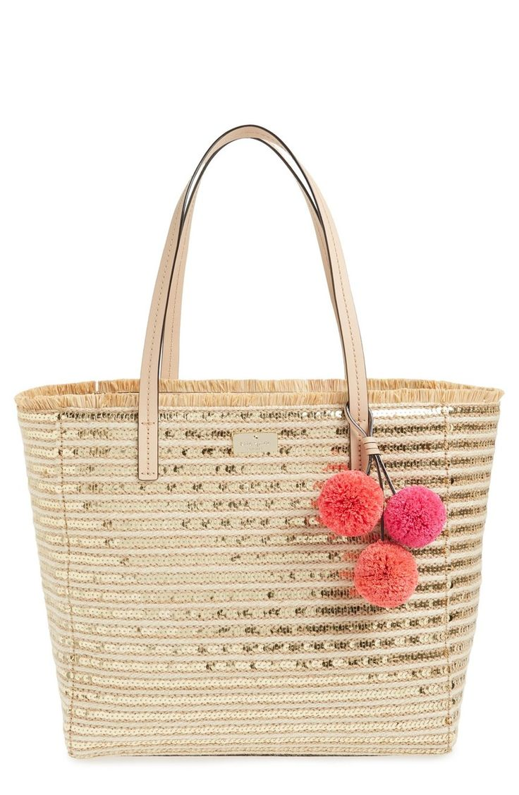 Putting a glam twist on a classic beach style! This woven tote from Kate Spade is covered in gold sequined stripes and features a colorful pom accent, dog-clip closure, and a spacious interior.