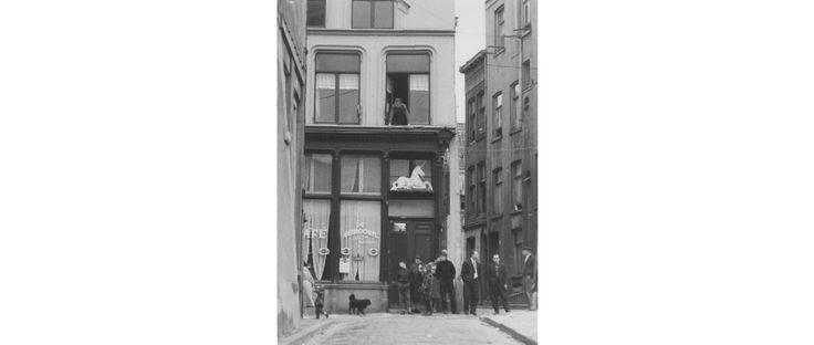 """Café """"De Eenhoorn"""" (later """"Het Witte Paard"""" geheten naar het wit geschilderd houten beeld van een liggende eenhoorn boven de cafédeur), op de ruit naast de deur staat de naam van de eigenaar Jan Duits. Gezien vanuit de Vosstraat,rechts de Steenstraat."""