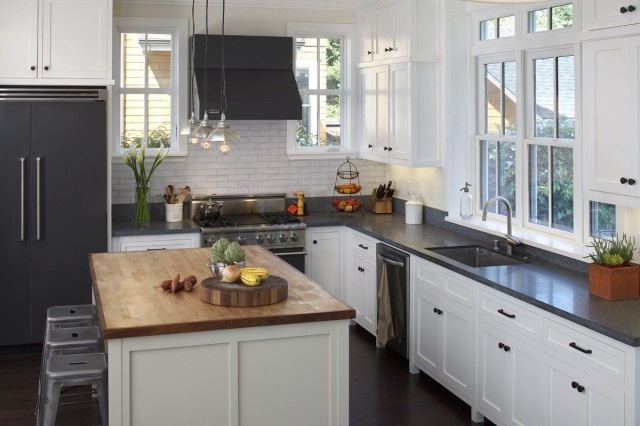 Artistic Designs for Living  Tineke Triggs    Gorgeous white & black kitchen with white shaker kitchen cabinets with honed black granite counter tops, light gray kitchen island with butcher block counter top, tolix stools vintage pendants, black fridge and range hood.