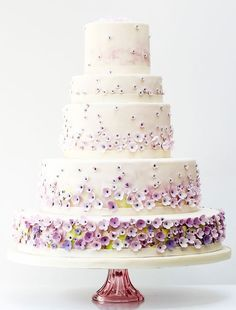 Tiny purple edible flowers on a big white wedding cake