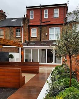 Addition of a Loft Conversion, Rear Extension with bi folding doors and a contemporary garden :   by REIS LONDON LTD