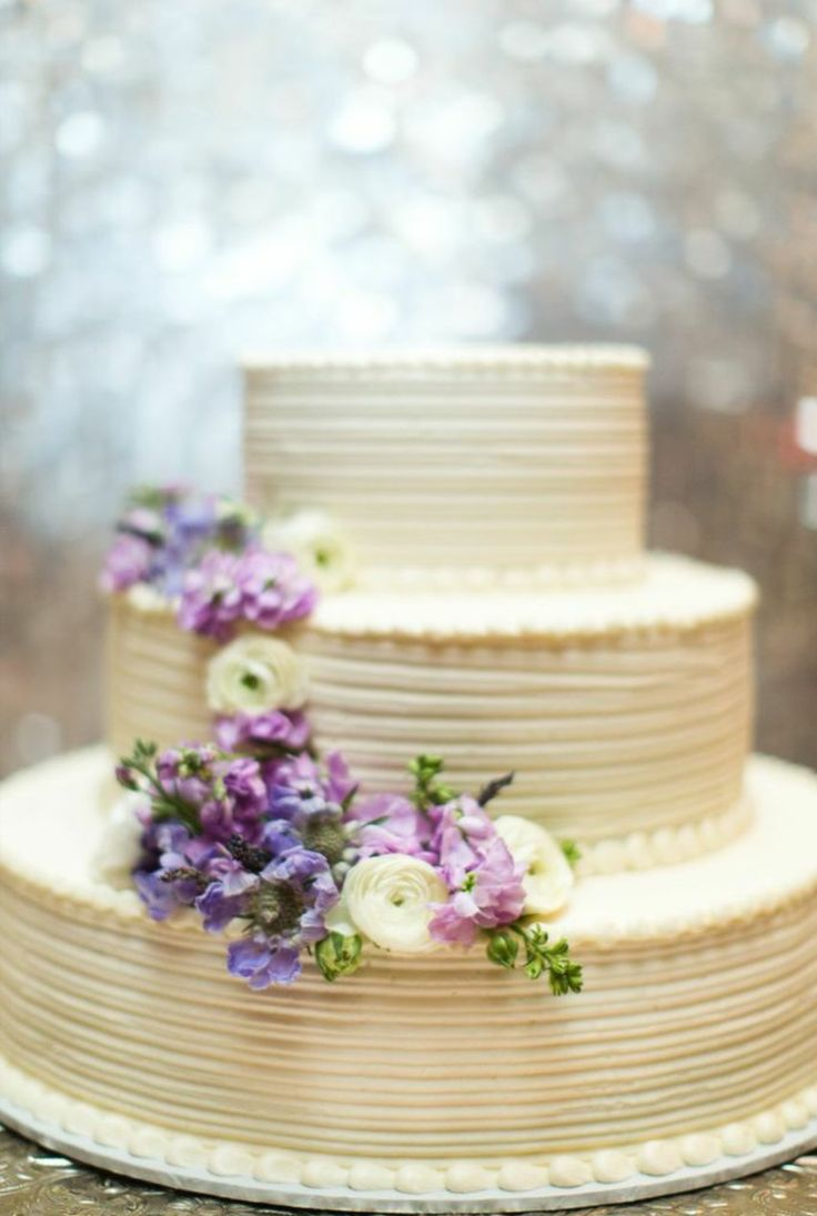 the cake was dressed with a waterfall of blooms. lavender stock, lavender scabiosa, & white ranunculus