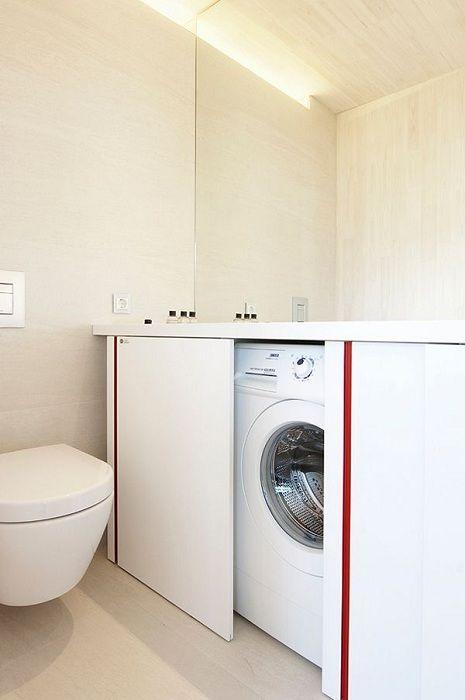 Un grande disegno opzione bagno con lavatrice nascosta con porte scorrevoli.
