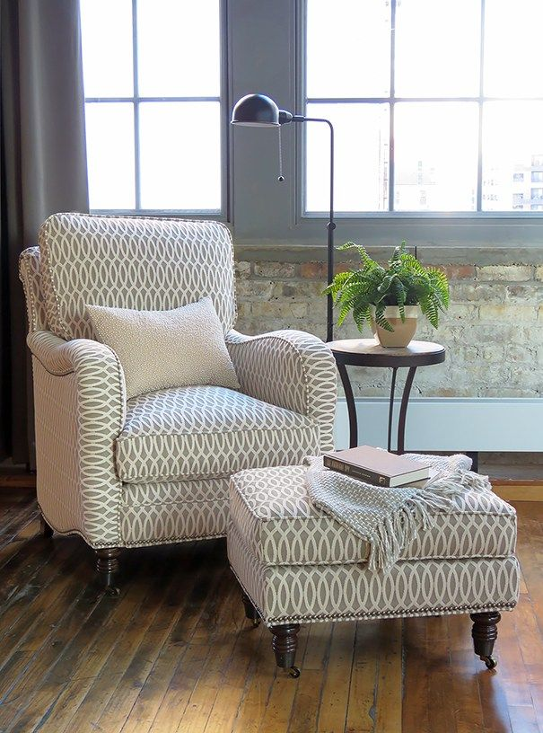 cozy nook with comfy accent chair and ottoman upholstered in a geometric print.  Loft space with aged wood floors, gray curtains, brick wall