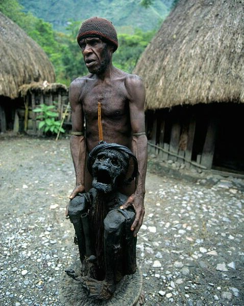 Dani tribesman showing mummified grandparent, Irian Jaya, Indonesia