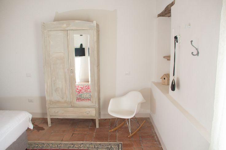 Kledingkast, Eames schommelstoel en perzisch tapijt (Nain) in eerste slaapkamer van ons vakantiehuis in Le Marche, Italie | Villa Fiore | Nu te huur!