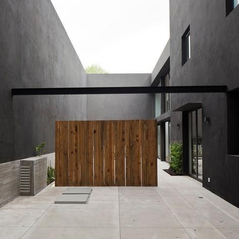 Wooden doors and screens stand out against the black walls of this house and courtyard in Mexico City.