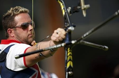 Britain's Larry Godfrey takes aim during the men's archery team eliminations at the Lords Cricket Ground during the London 2012
