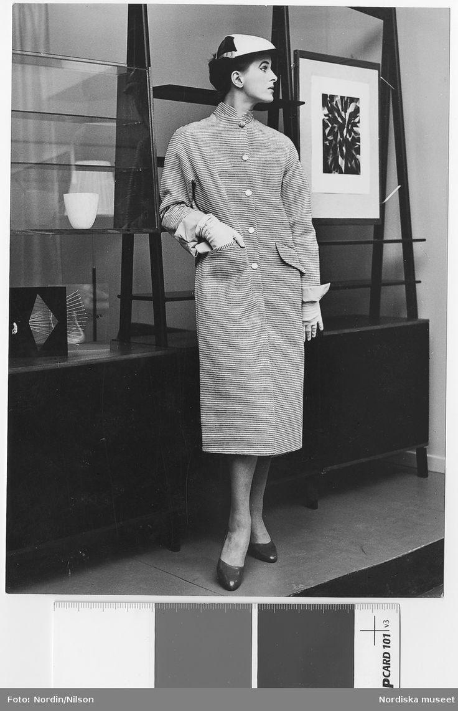 1955. Modell i hatt och vändbar kappa i svart/vit bomull med rosa, blått eller svart poplinfoder. Paramac, pris: 175:-. Konfektion. Framför hylla och tavla. Nordiska Kompaniet. Fotograf: Nordin/Nilson