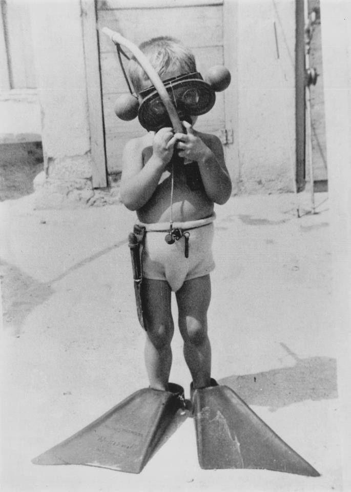 """Jordi Monjo (1948). Lleva una máscara Nemrod Asteria modelo semicircular con bolas y unas aletas Natación mod. SUPER-A. La máscara lleva lentes correctoras. El tubo parece ser el modelo """"Económico"""" de Nemrod y cuelga del mismo una pinza nasal. El cuchillo, en una funda de cuero, no he podido identificarlo aún. Al fondo se observa un fusil Nemrod modelo Fragata. Fuente: Facebook de Nemrod"""
