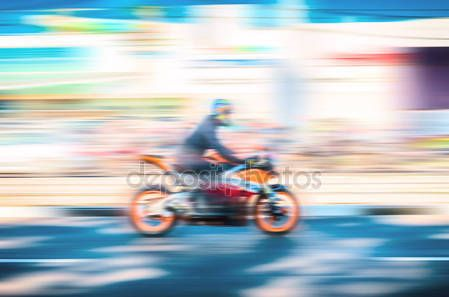 Blurred background with a fast-moving motorcyclist. The concept of speed, movement, motorsport