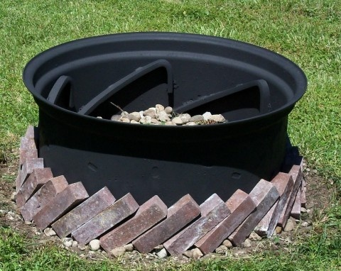 An old, re-painted tractor tire rim (painted with Rustoleum high heat paint), filled with rock and  used 30 bricks as edging.