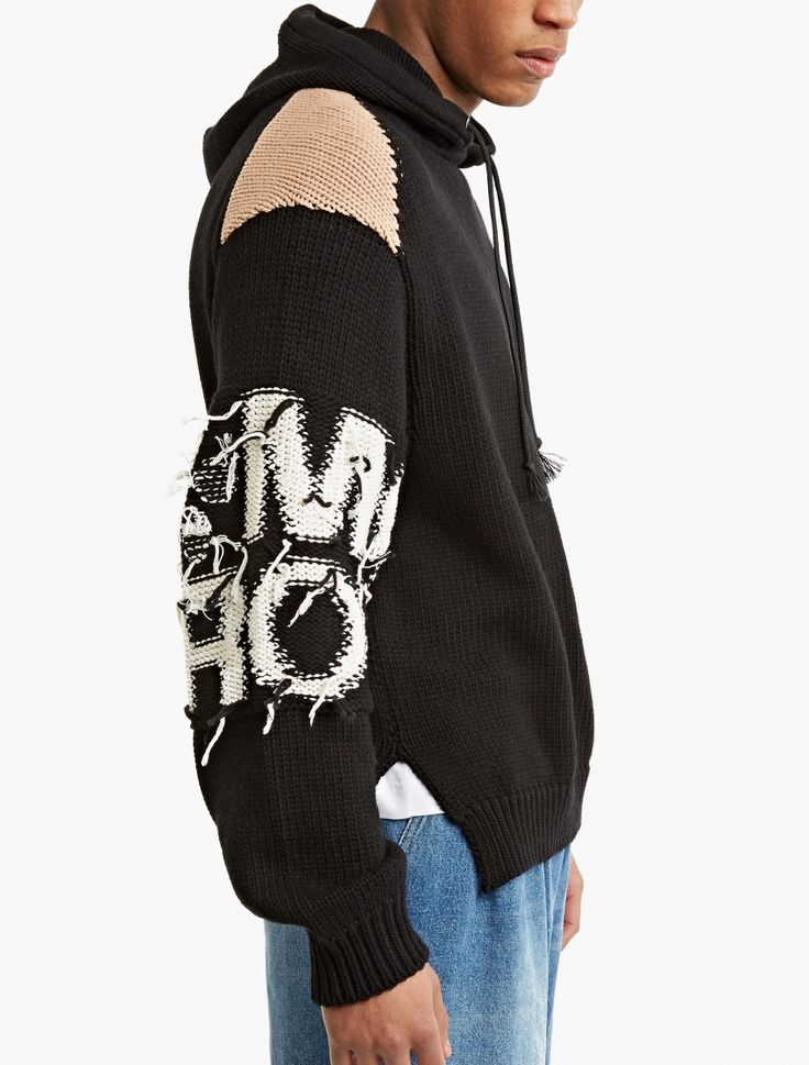 The Stella McCartney Tomorrow Knitted Hoodie for SS17, seen here in black.  A stand-out style from Stella McCartney's debut menswear collection, this chunky knitted hoodie features distinctive 'Tomorrow' text embroidered throughout. It is finished with an adjustable drawstring hood and contrasting panel detailing.