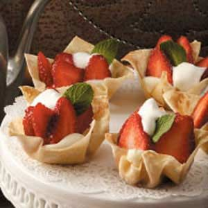 STRAWBERRY TARTLETS (from Best of Taste of Home, vol. 2) - contest winner; 12 wonton wrappers  3 tablespoons butter, melted  1/3 cup packed brown sugar  3/4 cup Mascarpone cheese  2 tablespoons honey  2 teaspoons orange juice  3 cups fresh strawberries, sliced  Whipped cream and fresh mint, optional