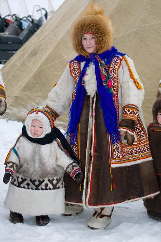 Christina, a Khanty women with her young son in traditional dress at a Spring festival in the village of Pitlyar. Yamal, Western Siberia, Russia