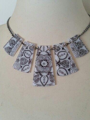 Shrink plastic necklace. Black design on white background.